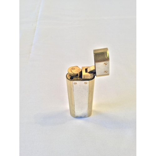 38 - Cartier 18k Gold and 925 Silver oval lighter. Stamped 750 on the base and 925 on the silver panel....
