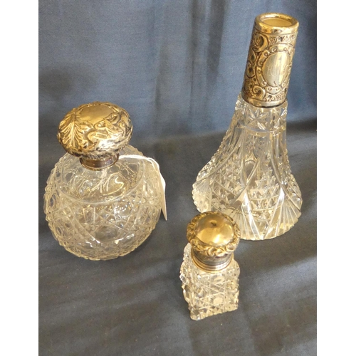1060 - Three Cut Glass Scent Bottles with Silver Mounts.