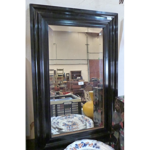 17 - An ebonised wall mirror with bevelled plate...
