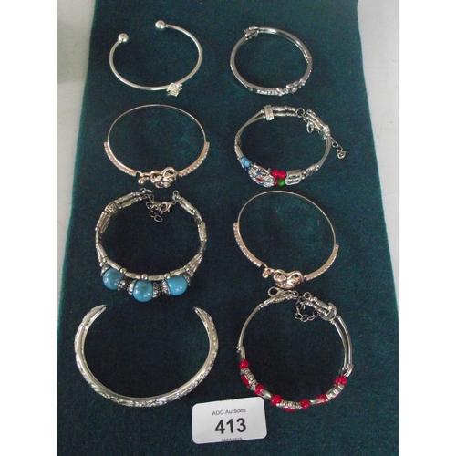 105 - 8 various white metal bangles...