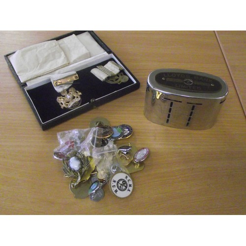 63 - Masonic medals, pin badges and a vintage Lloyds money bank with coins.