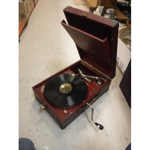 14 - A portable wind up gramophone together with a box of records, a vintage projector and two suitcases...