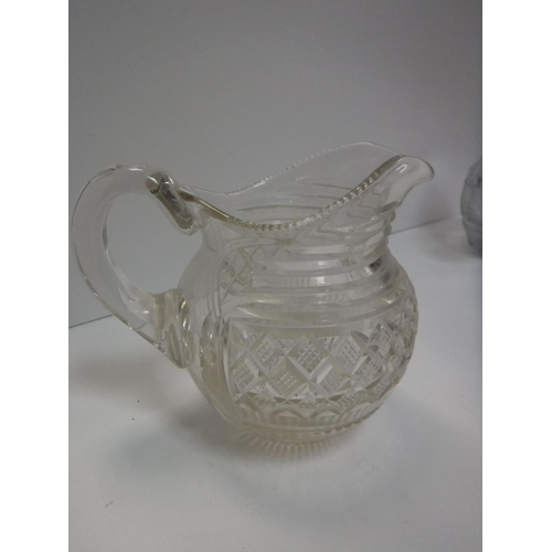 38 - A Georgian pineapple cut glass water jug with engraved bird amongst marguerites, wreath decoration 1...