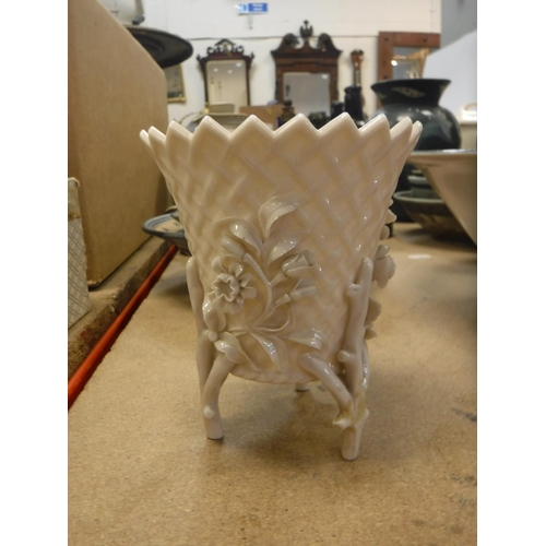 54 - A Beleek cream ware basket work and relief decorated vase on three branch supports with black Ferman...