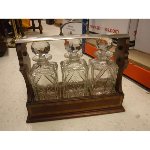 7 - An Edwardian style mahogany and inlaid three bottle tantalus with three cut glass decanters together...
