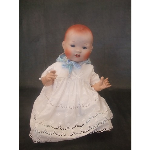 16 - An early 20th century Japanese bisque head doll with composition body, 34cm high....