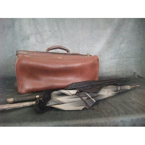 44 - A leather Gladstone bag and two parasols with metal mounts (3)...