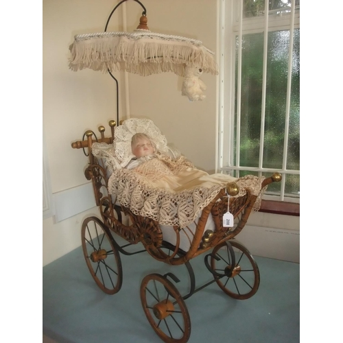50 - A bisque porcelain head doll, with plastic body, in a woven fibre and stained wood pram, 74cm long....