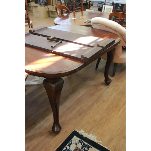 35 - A late Victorian mahogany wind-out dining table, on cabriole legs and pad feet, with castors, two ex...