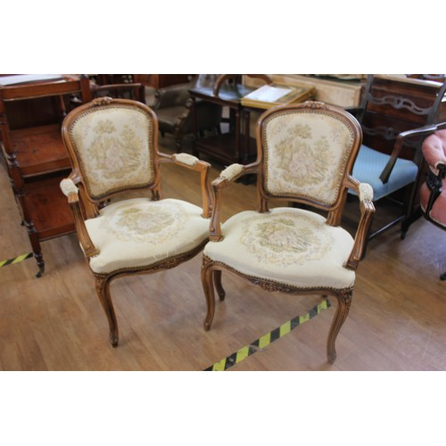 46 - A pair of reproduction carved beech fauteuils with tapestry upholstery on slender cabriole form legs...