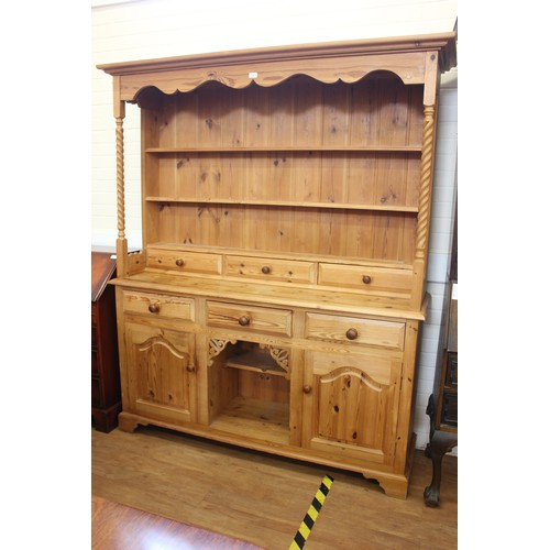 22 - A stripped pine dresser with plate rack and spice drawers, above drawers and panelled doors, 164cm w...