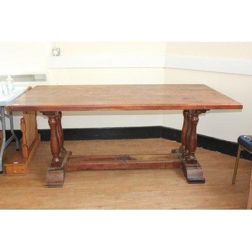 24 - A teak refectory style dining table of continental style, on triple turned end supports, scrolled tr...