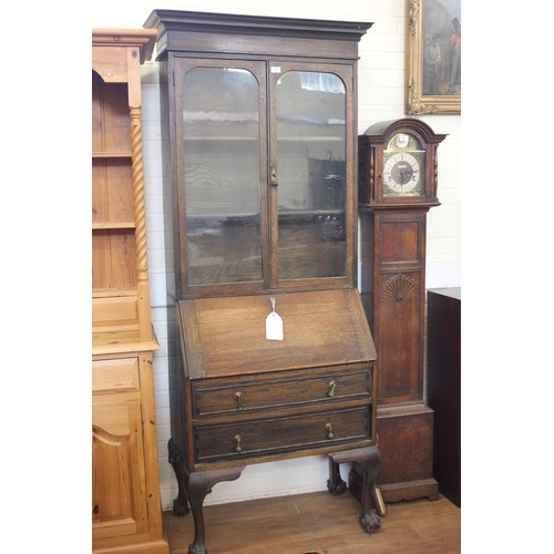25 - Oak bureau bookcase, the upper part with pair of glazed doors, writing flap below, fitted interior t...