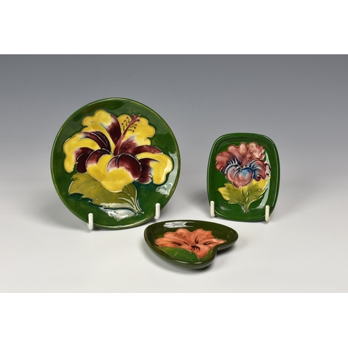 13 - Three modern Moorcroft Pottery trinket / pin trays, decorated with various hibiscus on green ground ...