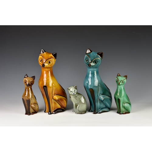 40 - Four Guernsey Pottery seated Siamese cat figurines, of varying sizes and colourways, the tallest 11¼...