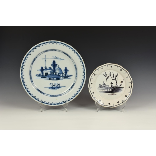 56 - A Delft blue and white charger, the centre decorated with houses and a pair of swans, 13¼in. (33.8cm...