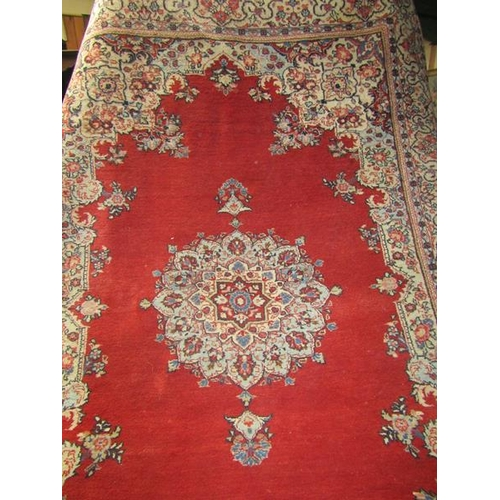 2042 - IRANIAN WOOLLEN RUG OF RED AND FORM GROUND FLORAL PATTERNED 162cms x 232cms