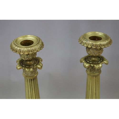 24 - Pair of antique French Empire style gilt candlesticks, having lion paw feet and fluted columns, each...