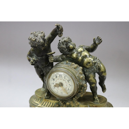 52 - Antique French figural ladies desk clock, surmounted with two putti, one feeding grapes, the other w...