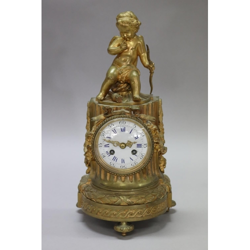 Antique 19th century French Louis XVI style figural gilt bronze, a putto surmounted to top, standing on tri legs. In working order at time of inspection. To include key & pendulum, approx 35cm H x 17cm W x 13cm D